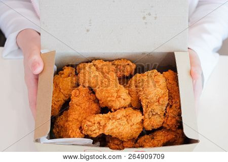 Hand Holding Delicious Crispy Fried Chicken Drumsticks & Wings For Snack Serve On White Boxes For Fo