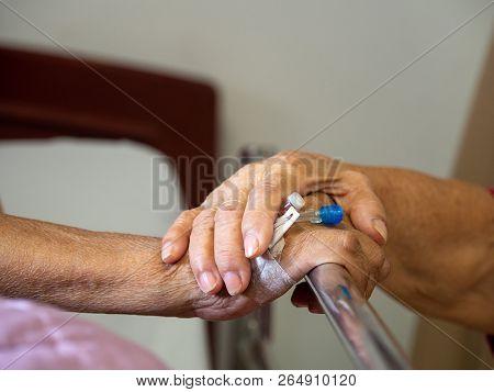 Wife Visiting Husband In Hospital. Senior Couple Holding Hands On Hospital Bed For Hospitalization F