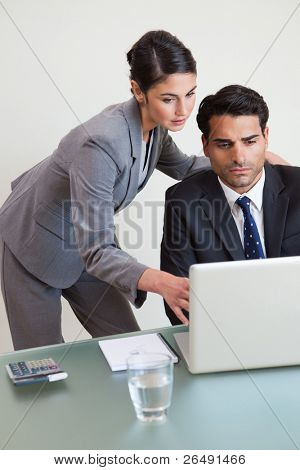 Portrait of a focused business team working with a laptop in an office