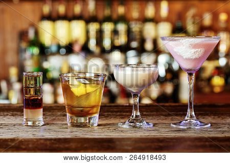 Different Cocktails On The Bar, Cocktails From Different Alcoholic Drinks In Glasses Of Different Sh