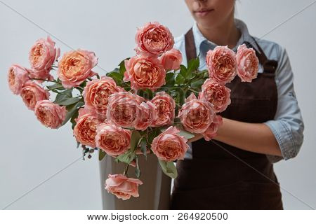 Woman florist with a bouquet of pink roses in a vase around a gray background. Floristics and business concept