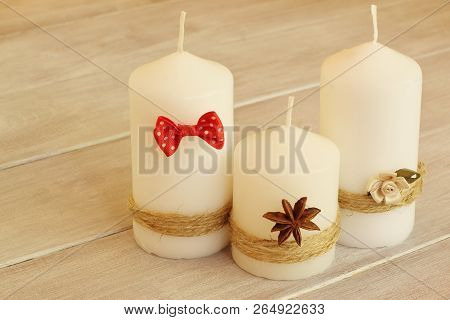 Family Holiday. Decorative Wax Candles Tied With Thin Jute Twine And Decorated With Red Bow Tie, Del