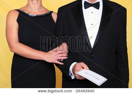Foto de um casal em desgaste da noite de black tie, o homem está segurando um convite.