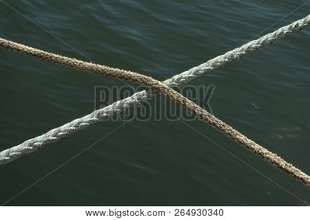Two Hennep Fiber Ropes Crossing Eachother In The Middle With A Ocean Water Background