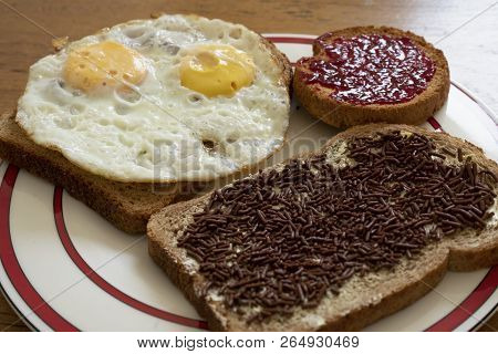 A Break With Well Done Eggs, Chocolate Milk Sprinkles And Raspberry Jam On Brown Slices Of Bread On