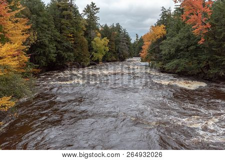 Autumn Colors Along The Presque Isle River Rapids In Michigan