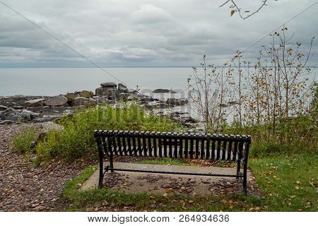 Park Bench Facing Rocky Shore Of Lake Superior In Northern Minnesota On A Cloudy Day
