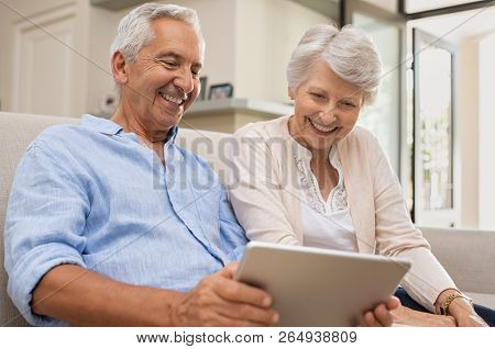 Senior couple using digital tablet sitting on couch at home. Happy old man surfing the net with his wife. Retired man and smiling elderly woman planning on summer vacation using tablet.