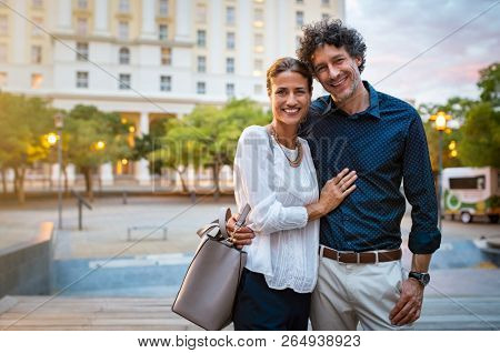 Smiling mature couple in smart casual embracing and looking at camera with city in background. Romantic handsome man and beautiful woman enjoying evening walk. Portrait of happy middle aged couple.