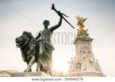 Low Angle View Of Gladiator And Lion Statue With Golden Angel Statues Against On A Pedestal Queen Vi