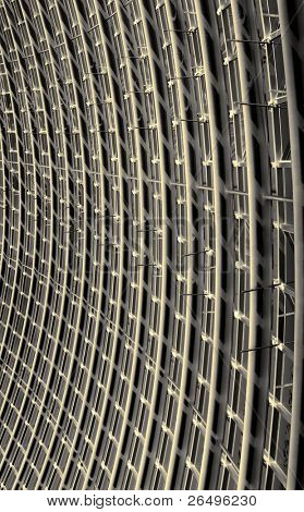 Abstract of the curved reinforced golden steel roof joists with blackened glass panes in between.