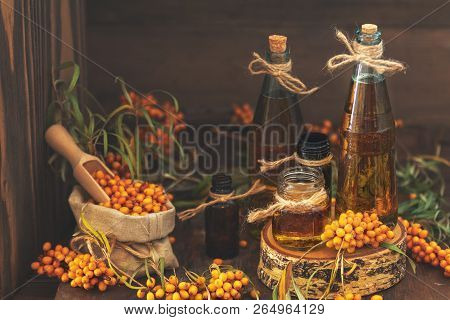 Natural, Organic Sea-buckthorn Berry In Linen Bag And Sea Buckthorn Oil In Glass Vintage Bottles On