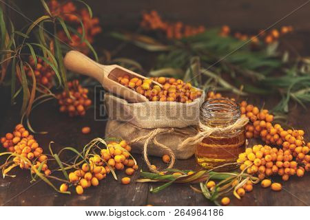 Natural, Organic Sea-buckthorn Berry In Linen Bag And Sea Buckthorn Oil In Glass Vintage Bottle