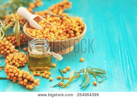 Natural, Organic Sea-buckthorn Berry In Bowl And And Sea Buckthorn Oil In Glass Vintage Bottle