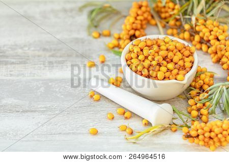 Natural, Organic Sea-buckthorn Berry In White Ceramic Mortar On Light Gray Wooden Background. Copy S