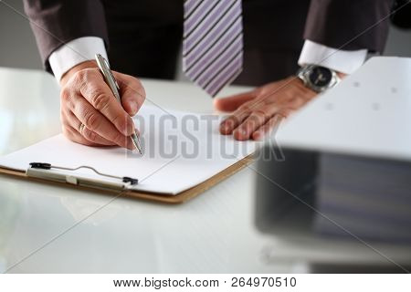 Male Arm In Suit And Tie Fill Form Clipped To Pad With Silver Pen Closeup. Sign Gesture Read Pact Sa