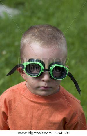 Kid Standing Poolside Wearing Googles With Serious Look.