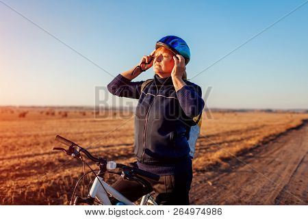 poster of Middle-aged woman bicyclist taking on helmet in autumn field at sunset. Senior sportswoman enjoying hobby.