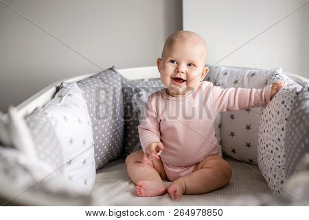 Funny Laughing Baby In A Pink Bodysuit, Sits In A White Round Crib, Around Light Pillows