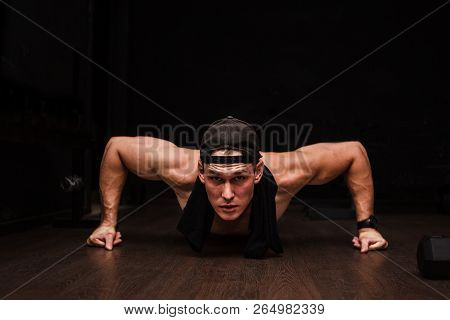 Young Adult Athlete Doing Push Ups As Part Of Bodybuilding Training.black Background