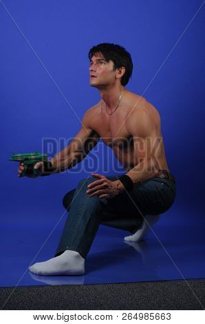 The sexy man prepares for battle with a weapon.