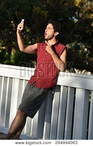 Young Man Taking A Selfie Outdoors Making A Goofy Face