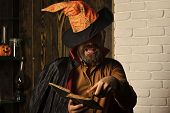 Halloween magic and evil spell. Man in witch hat and cloak. Mystic story, manuscript and fairytale. Wizard reading book on wooden and brick wall. Philosophy, wisdom and knowledge concept. poster
