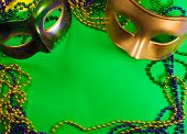 Two Mardi Gras mask with colorful beads on a green background poster