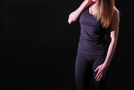 Athletic Girl In Tight Sportswear. Black Background.