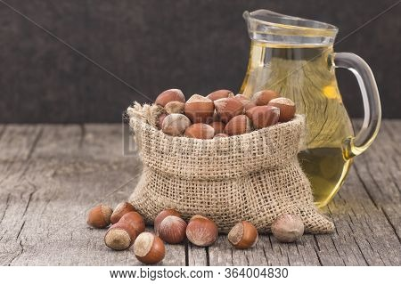 Hazelnuts, Filbert In Burlap Sack And Hazelnut Oil In Glass Of Bottle On Rustic Backdrop. Heap Or St