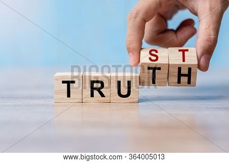 Businessman Hand Change Wooden Cube Block With Trust And Truth Business Word On Table Background. Tr