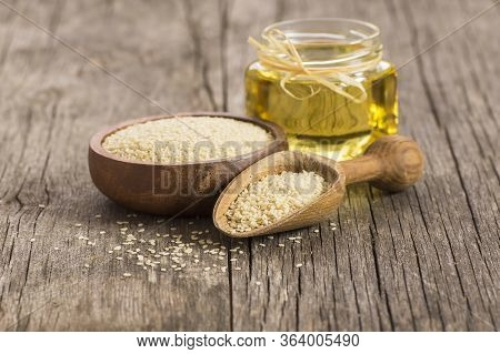 Glass Bottle Of Sesame Oil And Raw Sesame Seeds In Wooden Shovel With Burlap Sack On Wooden Table. U