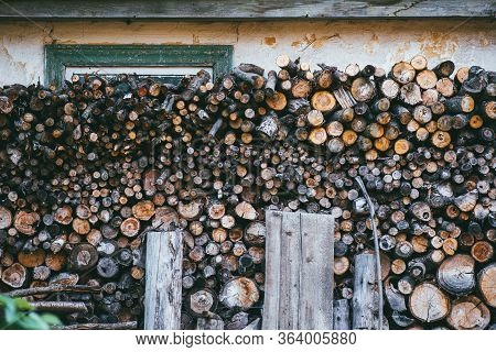 Woodpile With Firewood On A Background Of A House Wall Closes A Green Window