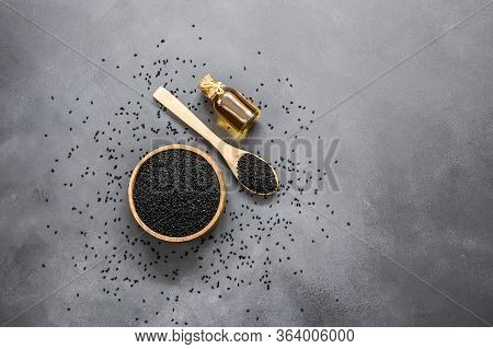 Glass Bottle Of Black Cumin Seeds Essential Oil , Nigella Sativa In Spoon On Rustic Table. Organic H