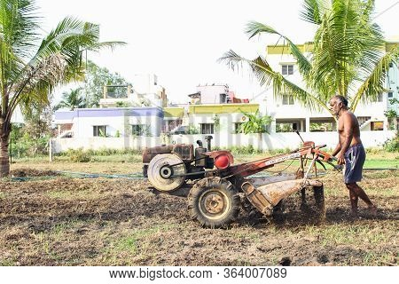 Old Perungalathur, Chennai, India. 25-april-2020: Framer Handing Mini Tractor On The Field And Plant