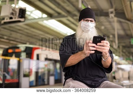 Mature Bearded Hipster Man Using Phone With Mask For Protection From Corona Virus Outbreak At Train