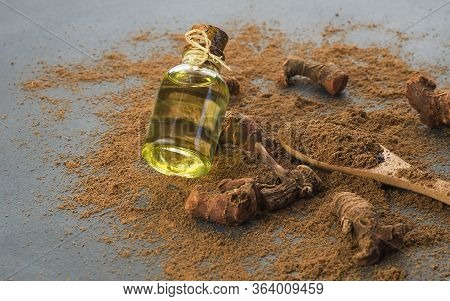 Glass Bottle Of Galangal Essential Oil, Root And Galanga Powder In Wooden Spoon On Rustic Table. Hea