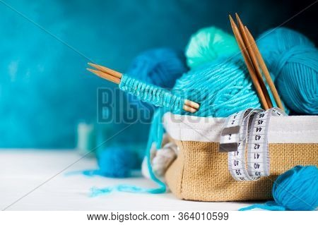 Blue And Aquamarin Yarn For Knitting In A Basket. Knitting Needles, Tape Measure, Glasses.