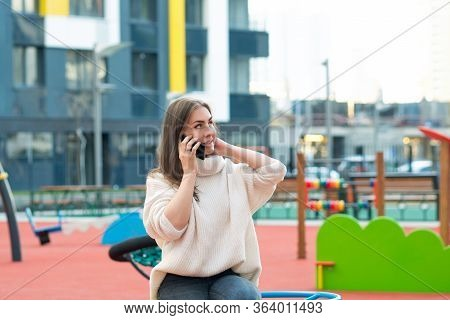 Young Woman Sits On Playground In Courtyard Of New Residential Complex And Speaks On Phone. Comforta