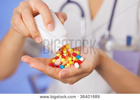 Pills, tablets and drugs pouring from bottle in doctor's hand on blue background