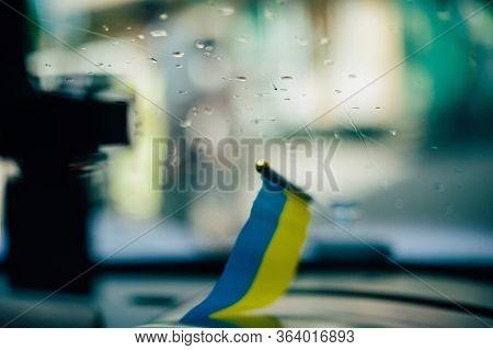 Ukrainian Flag On Glass Inside The Car. Ukraine Flag Outside The Window With Raindrops On The Glass.