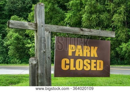 park closed  entrance or trailhead sign against green trees, restricted recreation during coronavirus covid-19 pandemic