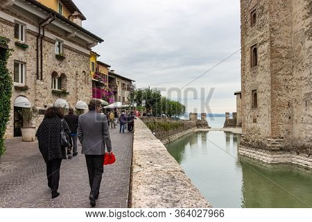 Sirmione, Italy, October 01, 2015 : Tourists Walk Along The Embankment Near The Castello Scaligero F