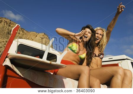 Low angle view of two women shouting while sitting on crew cab