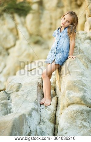 Brave Little Girl Sitting On A Rock At Sunset By The Sea. Tourism And Travel With Children. New Expe