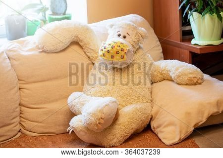 Big Childrens Toy Bear Of Vanilla Color In Yellow Medical Mask Is Sitting Sprawled On Sofa And Looki