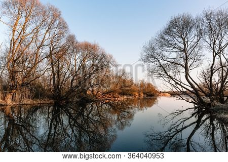 A Beautiful Blue River Along Bushes And Trees In The Rays Of Orange Sunlight. Reflection In The Wate