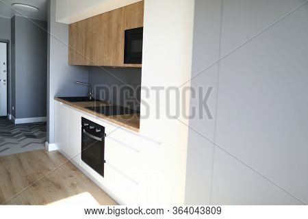 Close-up Of Kitchen Furniture In New Luxury Apartment. Room With Modern Interior Design. Black Sink