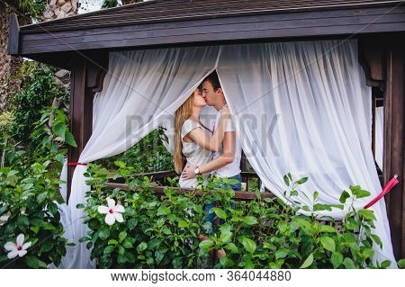 Happy Young Kissing Couple In Gazebo In Nature. Flowers Grow Near Wooden Installations For Recreatio