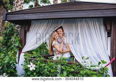 Happy Young Couple Embrace In Gazebo In Nature. Flowers Grow Near Wooden Installations For Recreatio